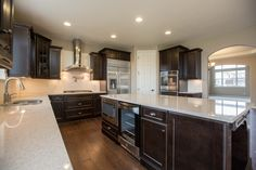 Fort Collins, CO - dark stained cabinets & white quartz counter tops #FindYourHome #DRHorton