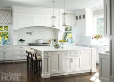 Traditional white kitchen seats three ivory leather upholstered curved back counter stools positioned in front of a large square white island fitted with white marble countertops lit by two Robert Abbey Cole Light Pendant.