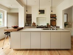 Contemporary Classic. An unusual mix of a classic Aga and a thoroughly sleek and modern kitchen sit easily together in this listed Georgian crescent terrace. kitchen design by Marcus Watkins, design manager, Kitchen Architecture. Published in November 2014 Utopia Kitchen & Bathroom magazine.
