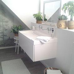 Badkamer in scandinavische stijl. Spiegel op een TV voet. Mooie oplossing voor badkamer met dakkapel.