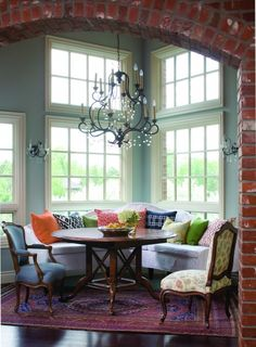 Built-in banquette.  Colorful pillows.  Exposed brick.  A fabulous chandelier.  Ceiling to floor windows for natural light.  Not one thing wrong with this room!  Beautiful.