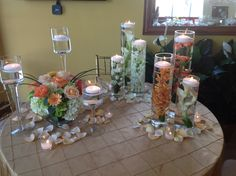 Staggered height cylinders filled with orange spray roses, orange orchids and white calla lily topped with floating candles.  Staggered height cylinders in all white.  Wedding centerpiece of white hydrangea, green hydrangea, coral gerbera daisy, pink roses and Free Spirit roses with monkey grass in clear glass cube surrounded  by a trio of pedestals with floating candles.  doristhefloristt.com