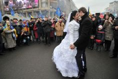 WEDDING DESTINATION: A bride and groom danced on Kiev's central square Friday as thousands of antigovernment protesters remained there behin...