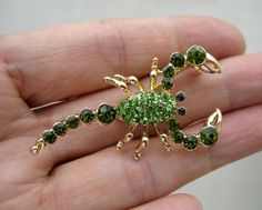Green Crystal Scorpion Pin Brooch by Brooch Collection by VenusDesigns. $8.99. This is a beautiful scorpion costume jewelry piece. Its body and claws are covered with green diamond genuine crystal rhinestones. Two black stones represent its eyes. It is attached with a securely safe pin closure