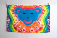 Wave it wide and high! This hand tie dyed large cotton flag features a blue and orange bear on a neon rainbow background. It has 1/2 wide sleeves on each side, so you can insert a dowel or thin flagpole, or thread a rope through to hang. Great for tailgating, music festivals, or to display all year round.  Flagpole is not included, but I can recommend one if you message me. Flag is cotton and not water proof.  **MEASUREMENTS**  Length 47 Width 29 Flagpole Opening 0.5  100% Cotton Machine...