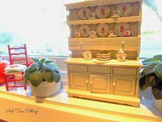 Dollhouse miniatures on the kitchen window sill.