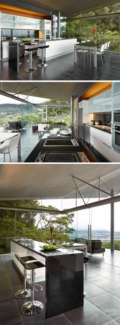 This modern kitchen has a large island with a dark countertop and additional room for counter stools. On three sides of the room are floor-to-ceiling windows, allowing guests to immerse themselves within the scenery.