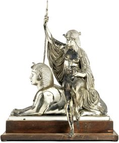 An Egyptian revival statue of a priestess seated on a sphinx (silvered bronze, late 19th century)