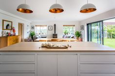 This island has flat panel cabinetry and is painted in Farrow & Ball All White. The oak worktop has been stained white and oiled. The hanging pendant lights above with copper inside add an industrial feel to a contemporary space. The open space plan incorporates the kitchen, living and dining room in a cohesive way.