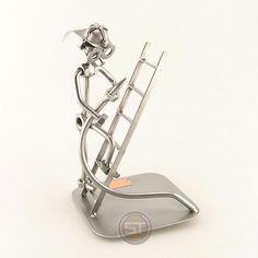 De brandweerman loopt met zijn brandweerslang de ladder op. Maten (h/b/d) in cm ca.: 19x12x12. Wilt u uw geschenk persoonlijk maken? Bestel er dan een grafeerbaar plaatje bij (artikel 10000). De metalen beeldjes zijn gemaakt in originele Steelman kwaliteit, uitvoerig en zorgvuldig handgemaakt. Als gevolg van deze afwerking is elk afzonderlijk metalenbeeldje uniek en voldoet aan de hoogste kwaliteitsnormen. Deze kleine stukjes van kunst die bestaan uit schroeven, moeren, metaal en koper ...