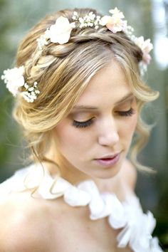A whimsical braided crown entwined with baby's breath adds a fresh feel to a loose updo.Photo Credit: Hair and Makeup by Steph