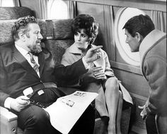 THE COMEDIANS (1967) - Peter Ustinov portrays a South American ambassador whose wife (Elizabeth Taylor) is having an affair with local hotel owner (Richard Burton) in revolution-torn Haiti - That's director Peter Glenville on the right - Based on the novel by Graham Greene - Directed by Peter Glenville - MGM - Production Still.