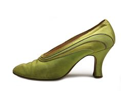 Green satin pumps decorated with silver leather piping at the quarters and vamp edge.