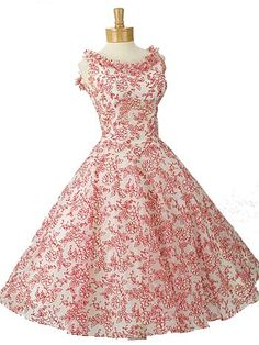 Showstopping vintage, red and white flocked organza, tea length party dress from the 1950s. Figure flattering fit and flared silhouette with adorable rhinestone trimmed organza flowers surrounding the neckline and very full, floaty skirt.