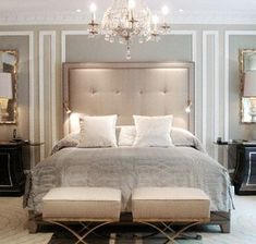 I love the glamorous look of a tall tufted headboard paired with an elegant chandelier.... AND those awesome ottoman/footstools at the end of the bed. #TallLamp