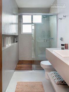 Exibindo revestimento cimentício, o banheiro ganhou deck de cumaru e pastilhas cerâmicas (Jatobá) no boxe. Projeto de Luciana Penna.