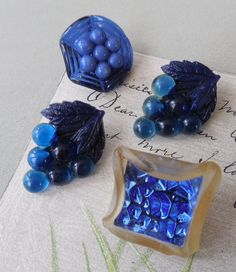 Heres a group of 4 vintage plastic buttons, all in dark blue. The two grape clusters are 1 long, the round bowl with beads is 3/4 in diameter,