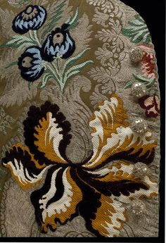 Detail embroidery, sleeved waistcoat, England (Spitalfields), c. 1734. Brown ribbed silk, richly brocaded with coloured silks, chenille and silver threads. The dense pattern of large flowers is typical of the 1730s, and corresponds to similar designs found in embroidery of the period. The lavish use of metal thread extends to the buttons, which are composed of a wooden core covered with silver foil and thread.