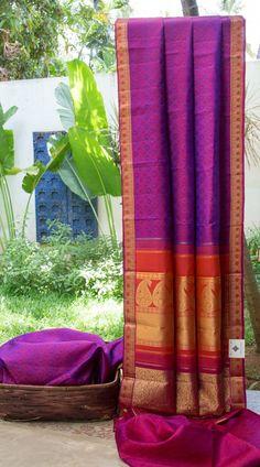 This violet and carrot orange shot sari has symmetrical thread brocade bhuttas all over the Kanchivaram silk fabric. The border has violet and carrot orange interwoven with gold zari. The pallu is ...