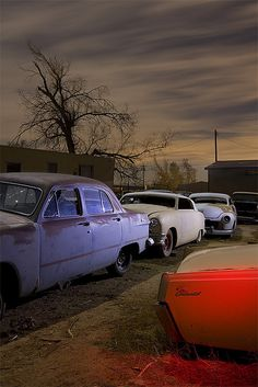 Behind Gene Winfield's Mojave Desert custom workshop is his own private junkyard. This backlot is packed with junker hot rods, never finished projects and forgotten treasures.   Night, combination of two 2-minute exposures. Full moon, natural LED flashlight and red-gelled strobe.