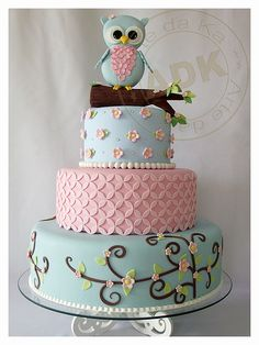 Owl baby shower cake. Blue Owl on Stem on 3 Tier Cake of Aqua with Brown Swirls and Pink Flowers, Pink Quartfoil and Blue with Pink Rosettes
