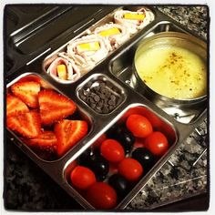 Strawberries, turkey and cheese pinwheels, olives and tomatoes, applesauce, and Enjoy Life choc chips!