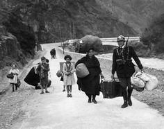 Un miembro de las tropas fronterizas francesas ayuda a una familia de refugiados que huyen de la Guerra Civil a cruzar la frontera de España, 1938.