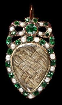 1775-1800, England. Gold set with pearls and green glass pastes, enclosing plaited hair. Hair had long been important in sentimental jewellery, but during the 18th century it took on a new prominence. It could now form the centrepiece of a jewel, arranged in complicated motifs or as plain, woven sections. Locket.