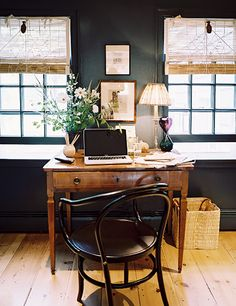 Pretty dark walls with desk between windows and Thonet chair