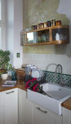 """""""Odkrycie archeologiczne"""" w postaci warstw starej farby na kuchennej ścianie dało ciekawy efekt."""