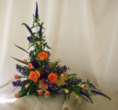 Asymetrical design with roses, carnations, veronica, monte casino, lily grass and heuchera leaves.