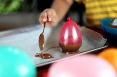 Brilliant idea for making edible chocolate bowls!  Dip balloons in melted chocolate and refrigerated them. Once they solidify, pop the balloons and removed the rubber.