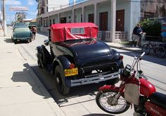 Banes, Cuba - 1930 Ford Model A coupe convertible.... with rumble seat) in Banes, Cuba and a Russian motorcycle