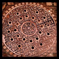 Manhole cover with cobblestones, SoHo, NYC