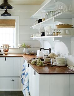 A paneled butler's pantry with open shelving, a charming sunken sink and butcher's block countertops is chock full of vintage charm and country style.