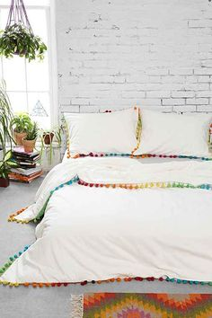 This would be fun with funky patterned sheets.  Comforter with pom pom edges in rainbow colors! Urban Outfitters.