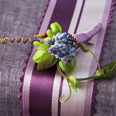The groom's boutonniere of grape hyacinths and passion vine is wrapped with patterned vintage ribbon to complement the bride's bouquet.