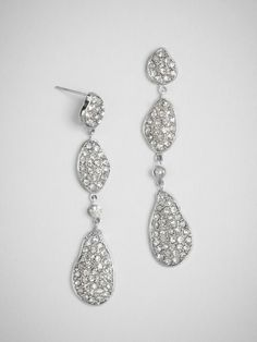 Fluid, metallic shapes are covered in pavé stones and accented with a single solo crystal. The organic shapes are ideal for an outdoor or whimsical wedding.