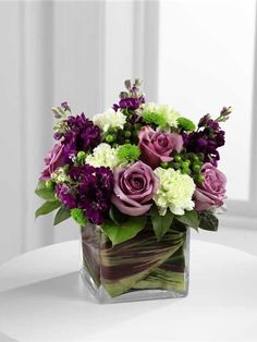 Compact leaf lined vase of purple flowers and green flowers
