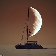 The half-moon has become this boat's wind sail as this photograph captures the exact moment they align