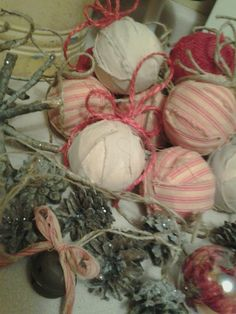 Rag ball ornaments made from Styrofoam wrapped with muslin and striped cotton ticking fabric hanging from red/brown jute.  Pine-cone ornaments sprayed with tac adhesive and sprinkled with glitter.  Rustic Christmas!