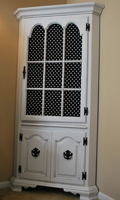 An old corner hutch finds a new life with a coat of paint and  polka dot fabric.