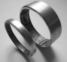 Simple metal wedding rings with their fingerprints inside