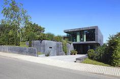 Eine durch die Absenkung notwendig gewordene Sockelmauer definiert die Einfahrt und führt geradewegs in das Haus (Südostansicht)