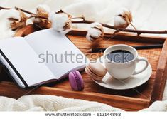 Cozy breakfast with cup of coffee, cotton flower, macaroon and open notebook on rustic wooden tray in bed.