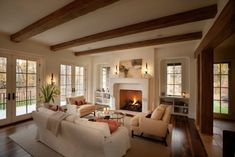 Cozy living room with wooden ceiling beams, dark wood floors, neutral couches, built-ins next to fireplace and double set of doors leading outside.