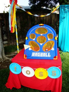 Use colored paper plates to create banners. Punch holes in the plates and thread ribbon through to create banners that spelled out names of games using precut letters and attached them with double-sided foam tape to make them pop out a little bit from the plates.