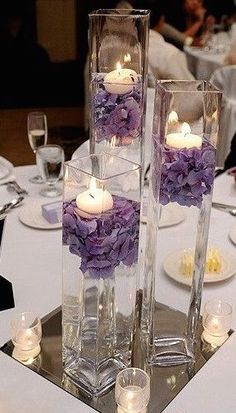 Simple purple centerpiece in staggered square vases....