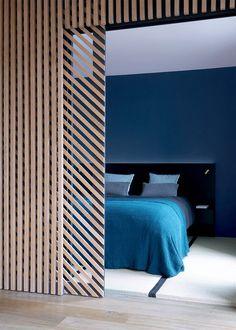 Une chambre bleue dissimulée par un mur en bois graphique - Marie Claire Maison