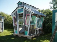 What a fantastic little greenhouse or playhouse or guest room constructed from salvaged material.  It looks like an old fashioned school house.